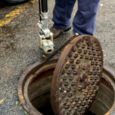 an employee opens a man hole cover to checks a portion of the sewer