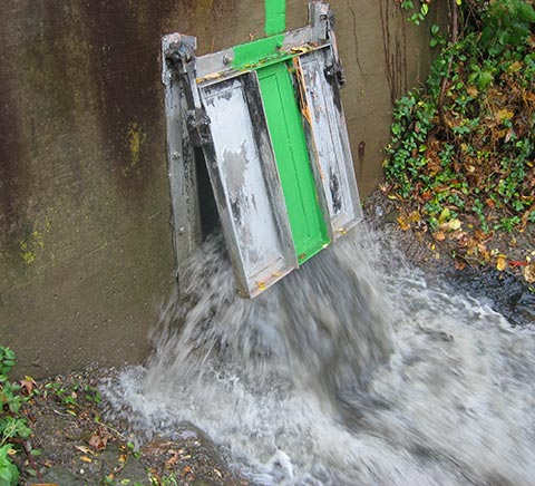 Stormwater overflowing out of a metal and wood door into an outside runoff area